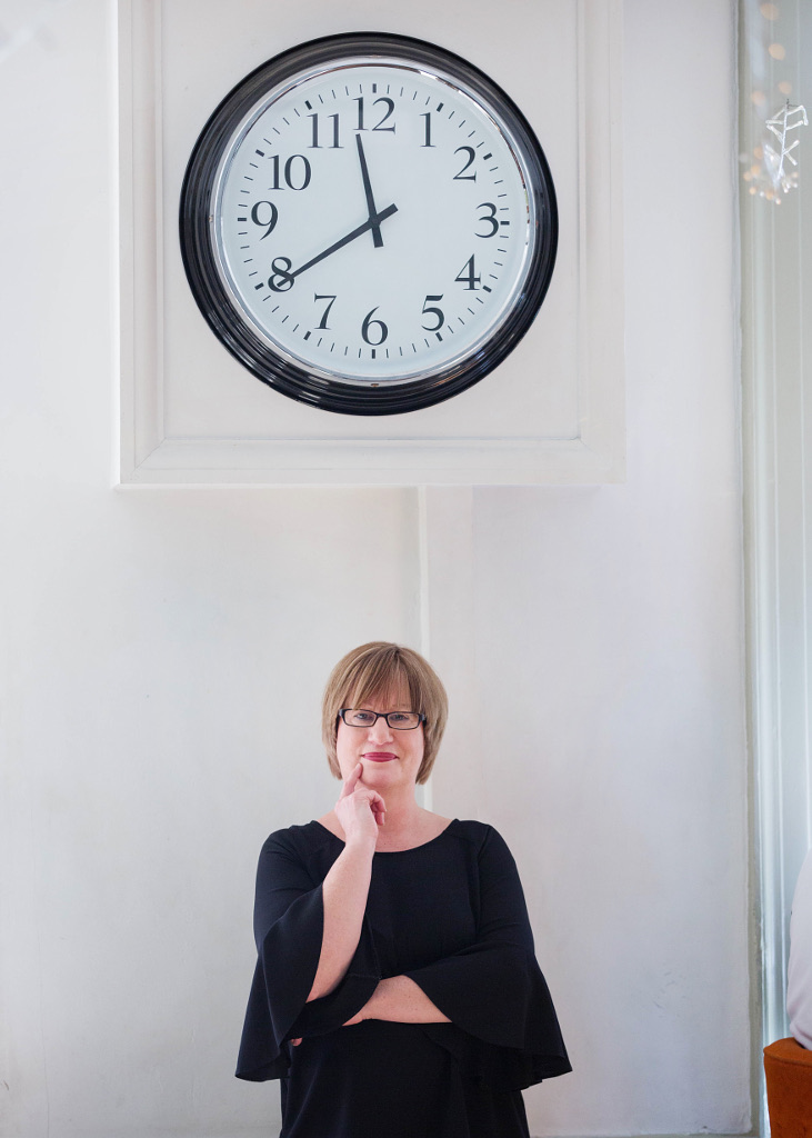 Copywriter Helen Gent in front of a large clock on wall