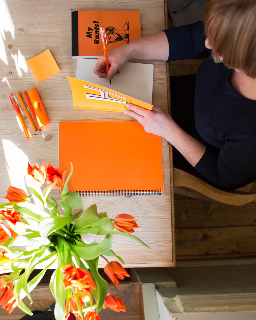 Blogger Helen Gent writing in yellow notebook at desk with orange stationery and orange pens and orange tulips