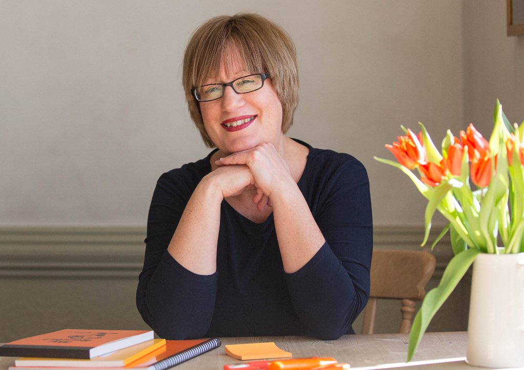Content creator Helen Gent sitting at desk with orange tulips and orange stationery