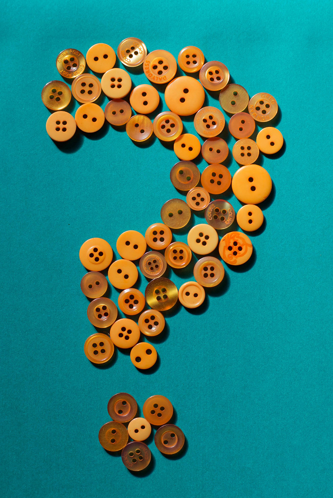 Question mark made out of orange buttons on a green background
