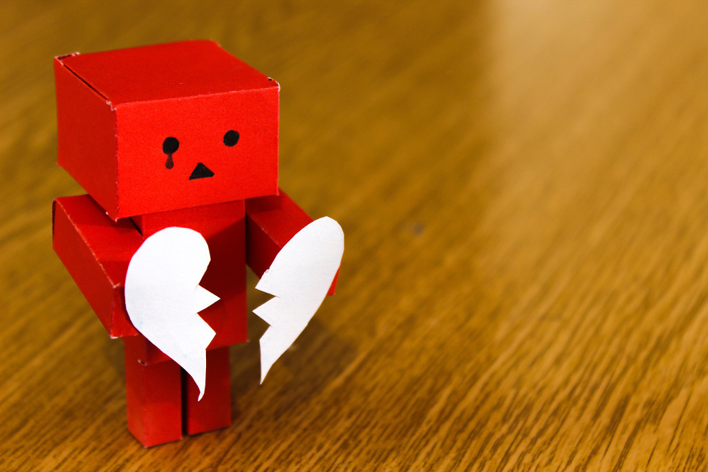 Little robot made out of red cardboard holding a white broken heart