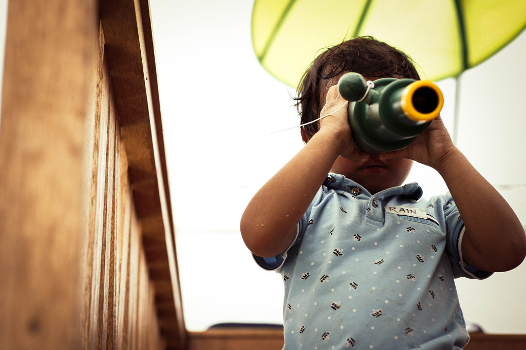 Young boy looking through a monoscope