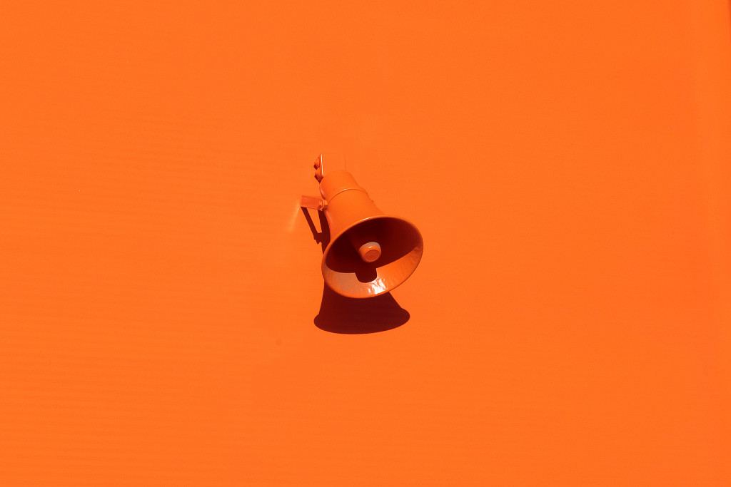 Orange loudspeaker on an orange wall