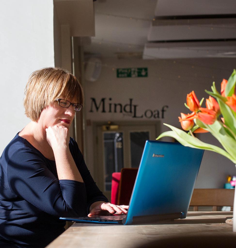 Web content writer Helen Gent working at blue laptop